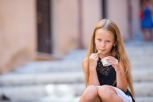 Adorable girl eating ice-cream outdoors at summer in the city