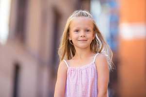 Adorable happy little girl outdoors in italian city. Portrait of caucasian kid enjoy summer vacation in Rome