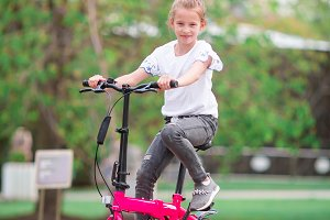 Adorable girl riding a bike at beautiful summer day outdoors