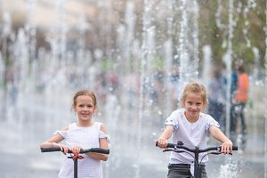 Little girls having fun in outdoor fountain at hot day