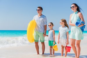 Happy beautiful family on a tropical beach vacation going to swim