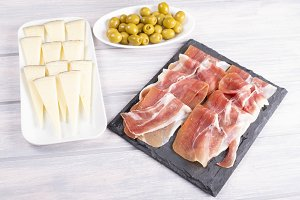 Ham, cheese and olives on wooden table. Typical tapas of Spanish cuisine.
