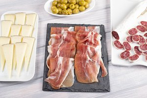 Ham, cheese and olives next to sausage on wooden table. Typical tapas of Spanish cuisine.