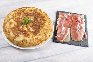 Potato omelet together ham on wooden table. Typical spanish food.