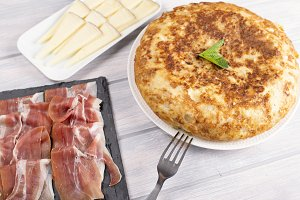 Omelette with ham cheese next to fork on wooden table. Typical spanish food.