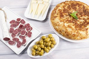Omelette with cheese, sausage and olives on wooden table. Typical spanish food.