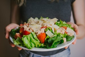 Girl holding plate with fresh salad