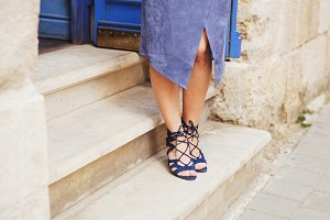 Legs in blue suede leather sandals