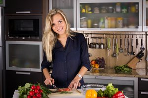 Young pretty young woman cooking salad in kitchen
