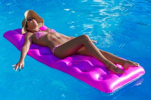 Young slim brunette woman in straw hat gets suntan on an air mat