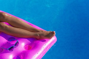 Young slim woman's legs on an air mattress in swimming pool