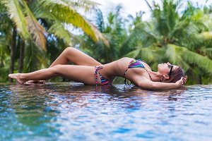 Young slim brunette woman sunbathe in tropical swimming pool