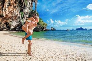 Happy couple in love boyfriend carrying his girlfriend in sea on tropical beach