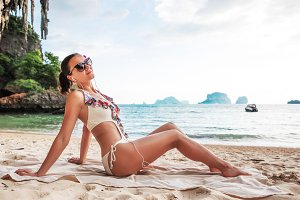 Young pretty slim brunette woman in sunglasses getting suntan on tropical beach