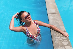 beautiful young slim brunette woman in sunglasses sunbathe in swimming pool