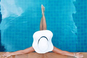 Young slim woman in straw hat sitting in swimming pool tropical