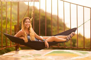 Young slim woman in tropical exotic hammock sunset lights