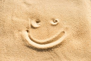 Smile sign drawing on sand