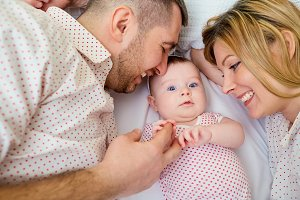 Mother and father with smiling baby lying