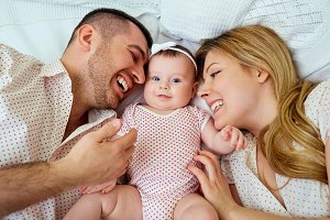 Mother and father happy smiling with her baby lying  the bed. Pa
