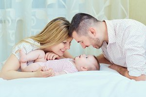 Mother and father playing with baby on the bed. A happy family