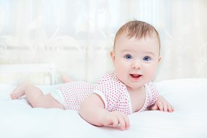 Cute baby smiling while lying on a white bed