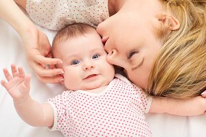 Mum kisses baby on the bed