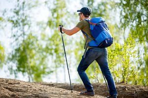 Image from back of man with backpack and walking sticks on hill