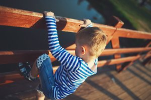 little boy climbing over the fence