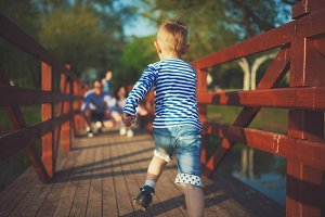 funny boy running on wooden bridge
