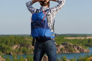 Photo back of tourist man with backpack with hands behind head on hill against backdrop of mountain expanses, blue sky