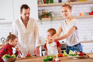 Picture of young mother and father with son and daughter preparing breakfast