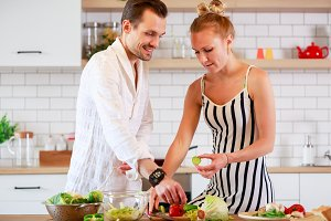 Photo of young woman and man preparing breakfast in kitchen at apartment
