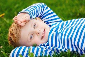 little boy lying on the grass