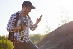 Photo of tourist man with walking sticks and telephone on mountain hill