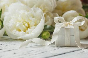 Bouquet of white peonies and present