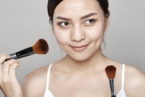 Close up studio portrait of pretty asian woman with soft skin holding makeup brush