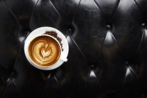 Coffee latte art with Leather sofa background