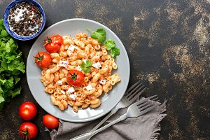 Italian dish of pasta with feta cheese and baked tomatoes on a dark background. Flat lay, copy space.