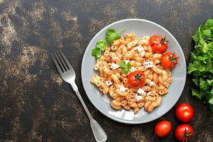 Macaroni with feta cheese, sauce and baked tomatoes. Italian dish. Dark background, flat lay.