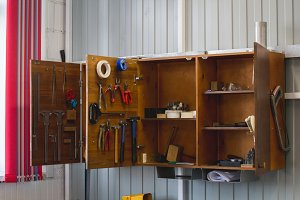 Open wooden cupboard with working tools