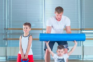 Group of children doing kids gymnastics in gym with teacher. Happy sporty children in gym. foam roller