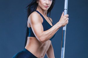Brutal athletic sexy woman holds a barbell. The concept of exercise sports, advertising a gym.Isolated on a black background.