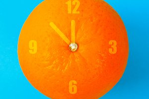 A clock in the form of an orange on a blue pastel background. Minimalism. The concept of summer, time.