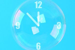 Soap bubbles with arrows in the form of a clock on a blue pastel background. Minimalism. The concept of elusive time.