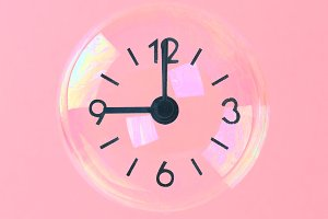Soap bubbles with arrows in the form of a clock on a pink pastel background. Minimalism. The concept of elusive time.