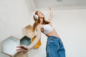 Leisure, home and technology concept - happy young woman in white headphones listening to music from smartphone and dancing on bed at home. She wearing white bra and blue jeans