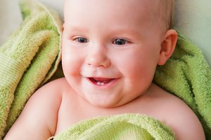 Smiling baby lying on bed