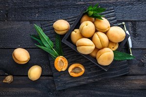 Delicious ripe apricots in a wooden box on dark background