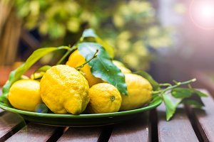 Lemons with leaves in a green bowl on a wooden table.